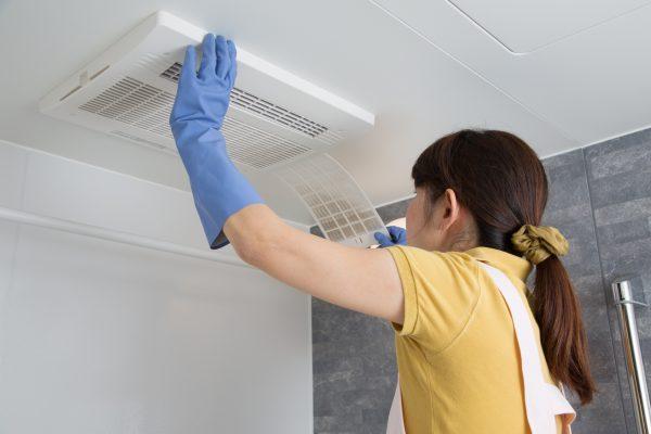 お風呂場の換気扇を掃除している主婦