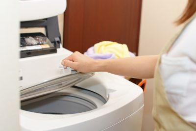 洗濯機で洋服を洗濯している主婦
