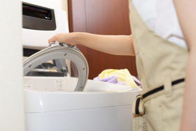 洗濯機を使っている女性