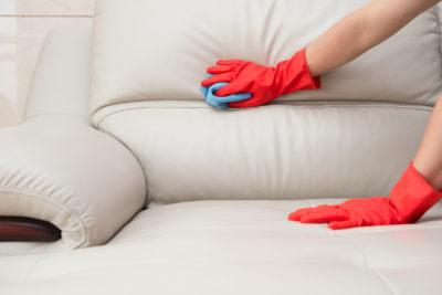ソファーを掃除している女性