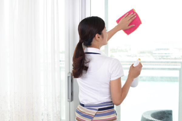 窓を掃除している主婦