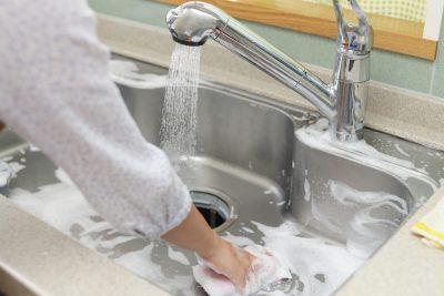 キッチンのシンクを掃除している主婦