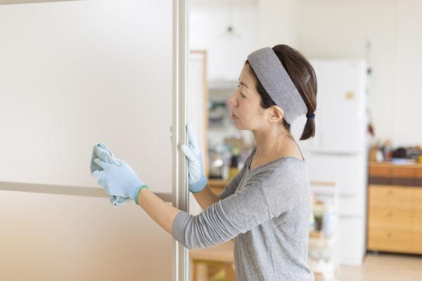 扉の掃除をしている女性
