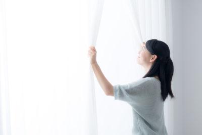 カーテンを開けている女性