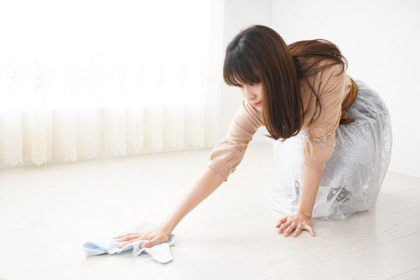 部屋の床を掃除している主婦