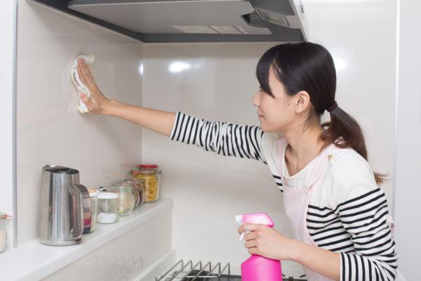 キッチンの壁を掃除している女性