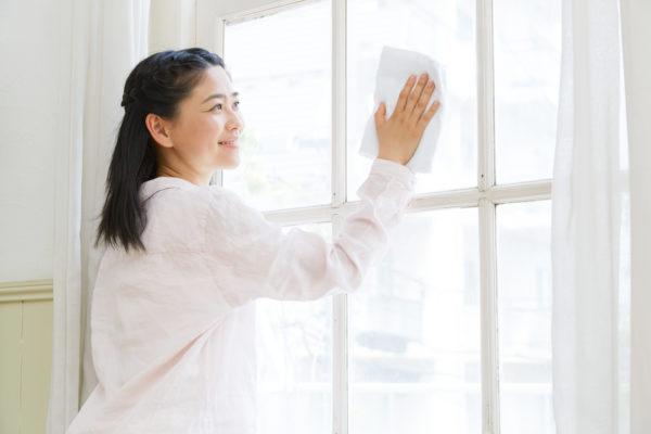 窓ガラスを拭いている女性