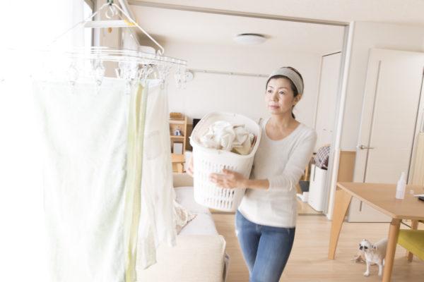 洗濯物を部屋で干している主婦