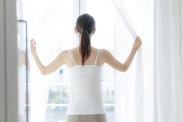 カーテンを開けて外を眺めている女性