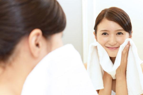 清潔なタオルで顔を拭いている女性