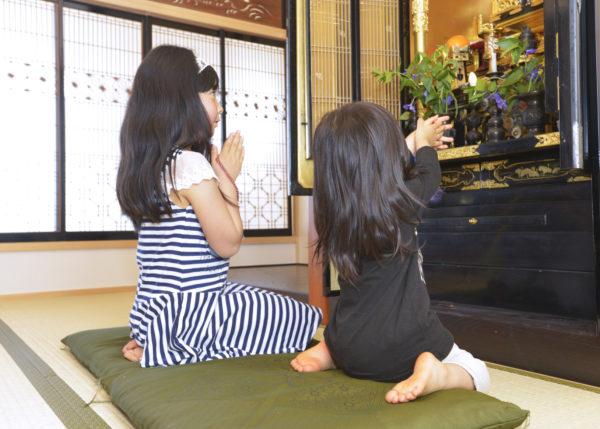 お仏壇に手をあわせる姉妹